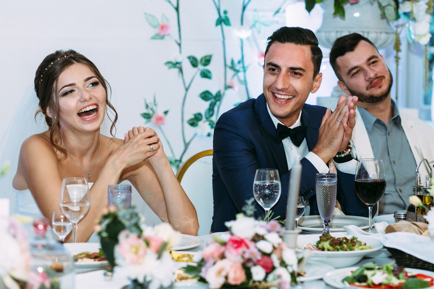 cheerful married couple at wedding reception dinner